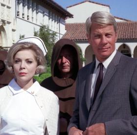 "Nurse Cinnamon (Barbara Bain) and Dr. Phelps (Peter Graves) are escorted into the monastery in ""The Cardinal"""