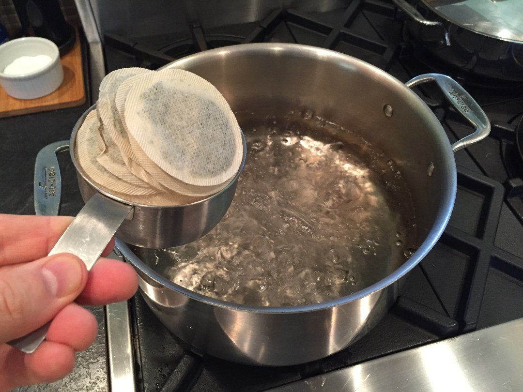 One gallon of water boiling on the stove top, and one cup of sugar and 8 tea bags about to be added