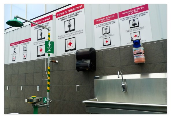 Washing station and emergency shower signage clearly lays out procedures in both English and Spanish.
