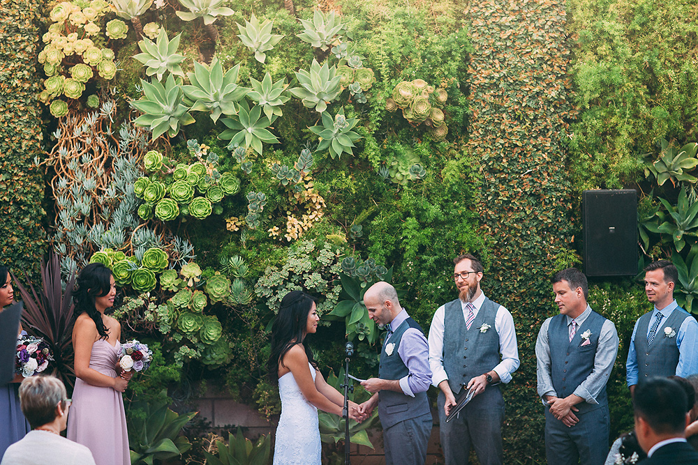 The happy couple mid-nuptials — just check out that succulent wall behind them.