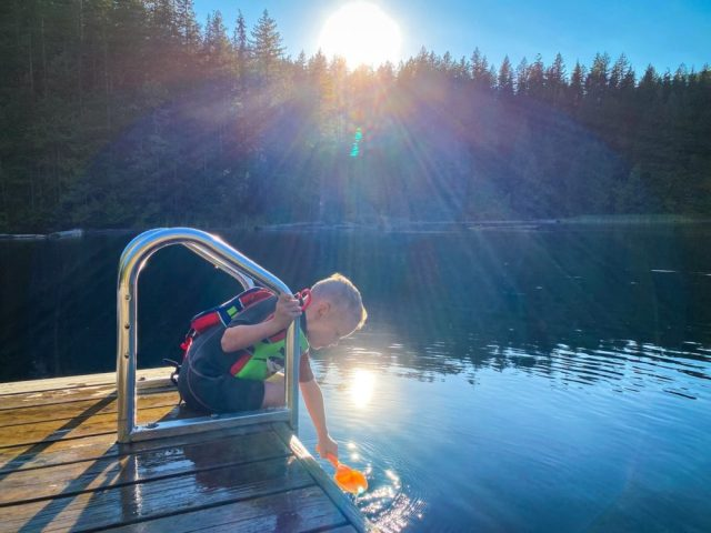 C Playing on the edge of the dock just as the sun goes over the mountain at the end of the day.