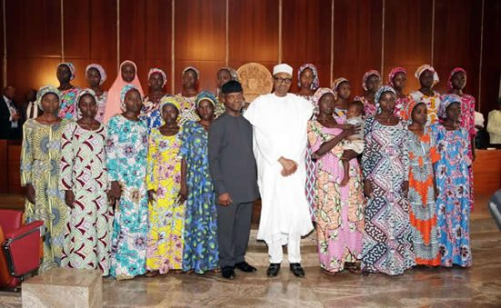 President Muhammadu Buhari and Vice President Yemi Osinbajo (M) flanked by the 21 Chibok girls