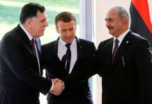 Emmanuel Macron, centre, with Sarraj, left, and Haftar as they shake hands after talks aimed at easing tensions.