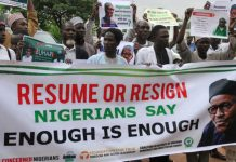Protesters carry placards to demand that ailing President Mohammadu Buhari resume work or resign in Abuja