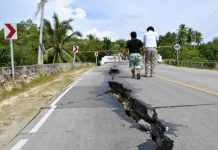 Residents walk along huge cracks in a road after an earthquake struck Bohol province, central Philippines
