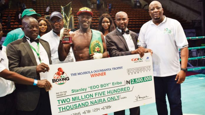 "FILE PHOTO: Stanley ""Edo Boy"" Eribo with the N2.5 million cheque after retaining his African Boxing Union (ABU) welterweight title by defeating Tanzania's Ramadhani Shauri via a unanimous decision at GOtv Boxing Night 12"