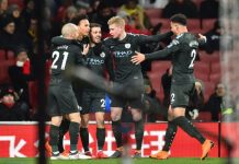 Man City players celebrate scoring the second goal at Arsenal