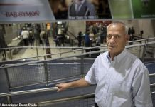 In this May 22, 2018, photo provided by the Institute for Justice in Arlington, Va., Rustem Kazazi poses for a portrait in Cleveland Hopkins International Airport in Cleveland. Kazazi, a U.S. citizen who immigrated from Albania in 2005, says in a lawsuit filed Thursday, May 31, 2018, that U.S. agents seized his life savings of $58,000 at the airport in October 2017, and the government has refused to return the money even though Kazazi faces no charges. A spokesman for the Customs and Border Protection said the agency doesn't comment on pending lawsuits. (Isaac Reese/Institute for Justice via AP)