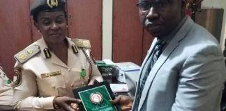 EFCC's Mr Isyaku Sharu presenting the watch list to Comptroller of Immigration Service, Kwara State Command, Edith Onymenam