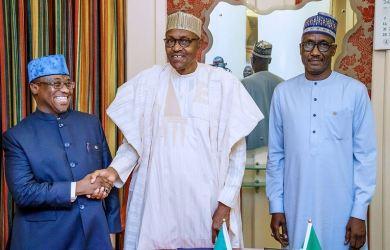 President Muhammadu Buhari shaking hands with Maikanti Baru as Mele Kyari looks on