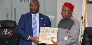 Chairman, Federal Inland Revenue Service (FIRS), Mr. Tunde Fowler, presenting a book on President Muhammadu Buhari to Chairman, Revenue Mobilisation, Allocation and Fiscal Commission (RMAFC), Chief Elias Mbam at the FIRS Headquarters in Abuja