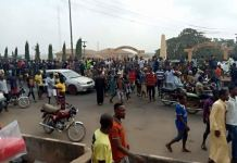 Protesters walk past the palace of the Akarigbo of Remo in Sagamu, Ogun State on Monday