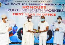 Lagos State Commissioner for Health, Prof. Akin Abayomi; Governor Babajide Sanwo-Olu, presenting a plaque to a Frontline Health worker, Dr. Sunday Oluseyi Adesola - Principal Medical Officer 1 at Isolation Centre, Mainland Hospital Yaba