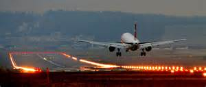 plane landing on a runway with lights on at dusk