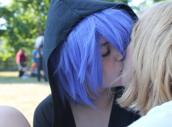 a blue haired woman with a black hooded sweatshirt had her hood up and is kissing a blonde woman in a white top