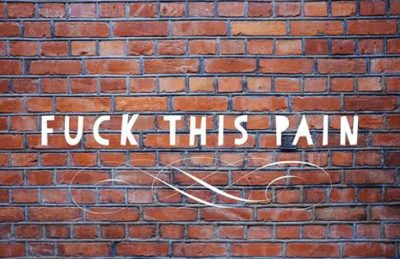 A brick wall with an overlay that says 'fuck this pain' and a fancy curly doodle underneath