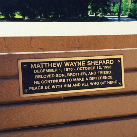 """bench with a placard: """"Matthew Wayne Shepard December 1, 1976 - October 12, 1998 Beloved son, brother, and friend he continues to make a difference peace be with him and all who sit here"""