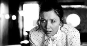 Maggie Gyllenhaal playing Lee Holloway; B&W photo; Maggie is in a white shirt with black polka dots and is leaning over a desk with a surprised look on her face