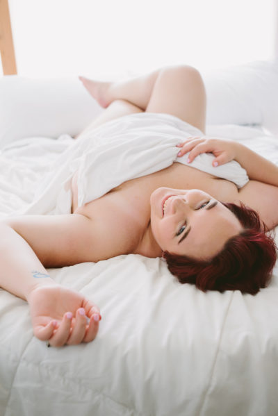 color pic of kirsten laying down tangled in sheets (which cover the good bits) on a white bed with short red hair; pic is taken from end of the bed so K is upside down, legs crossed and bent at the knees, right hand on sheet on chest, and left hand up beside her head; she's smiling/laughing