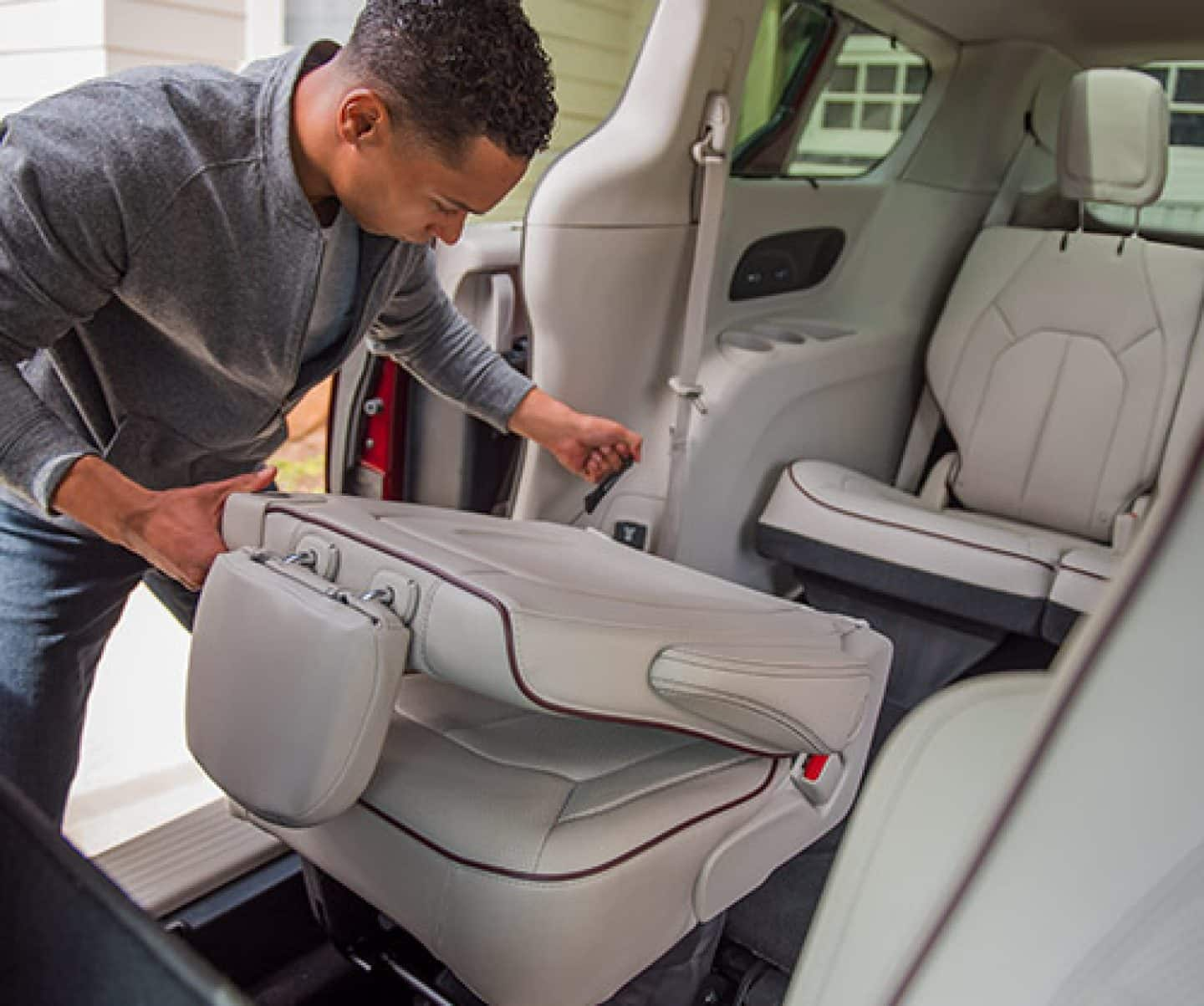hight resolution of man folding the second row seatback in a 2019 chrysler pacifica