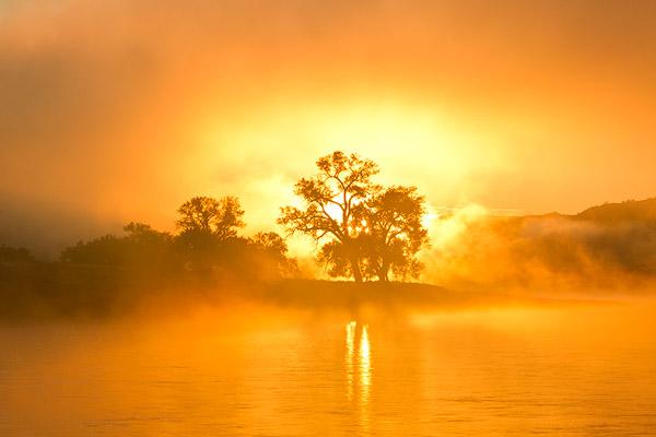 Morning sunrise burns through the fog on the Missouri River at the Upper Missouri River Breaks National Monument, Montana