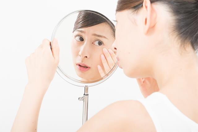 鏡をのぞき込んで肌トラブルの心配をする女性