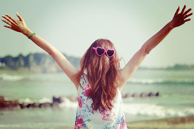 脱毛が完了して海に向かって喜ぶ女性