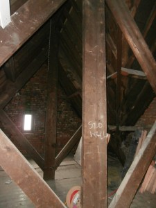 Exposed king post trusses adjoining the hipped roof to the right.