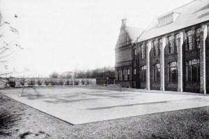 This 1900 image shows one tennis court directly behind the original High School building.