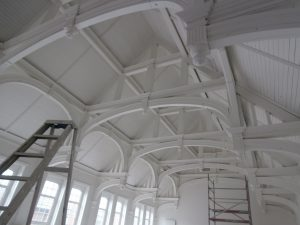 The bright, white Hall ceiling looking north towards the stage.