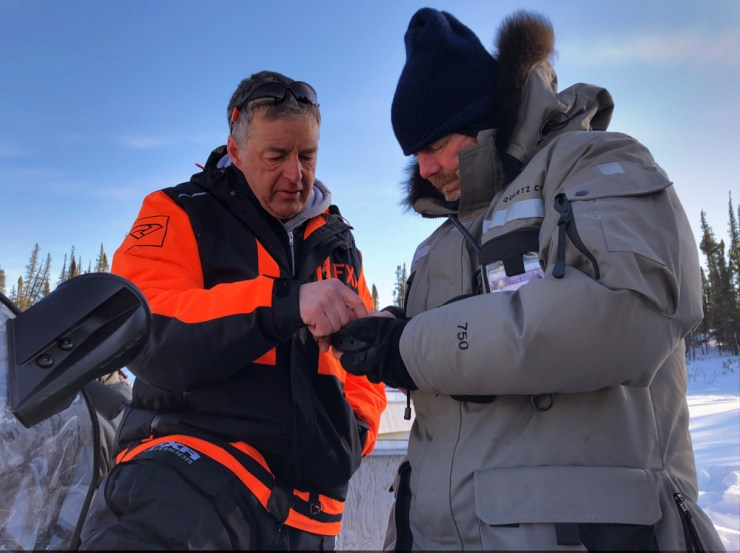 Churchill Wild co-owner Mike Reimer (left) and head guide Andy MacPherson consult a GPS to figure out which way a mother bear is headed.