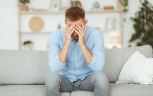Depressed guy sitting on couch, covering face with hands