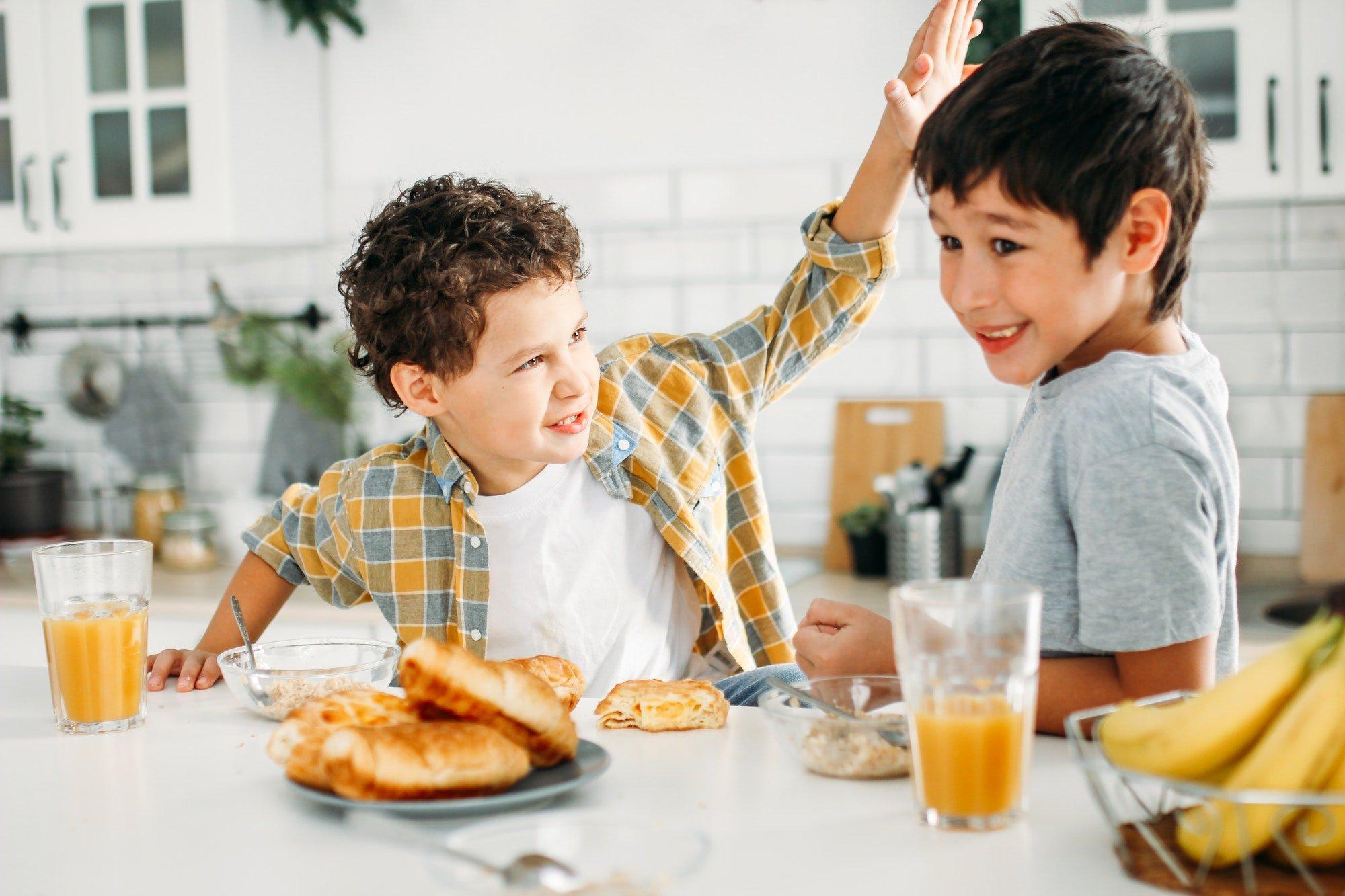 Two siblings tween boys brothers having breakfast on kitchen