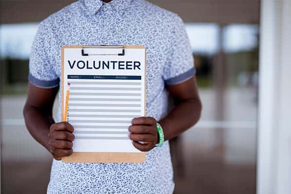 man holding volunteer clipboard to recruit volunteers in church