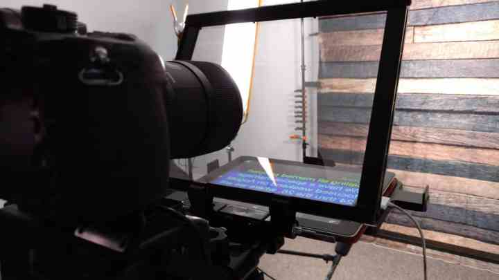 a dslr camera pointing through a teleprompter mirror