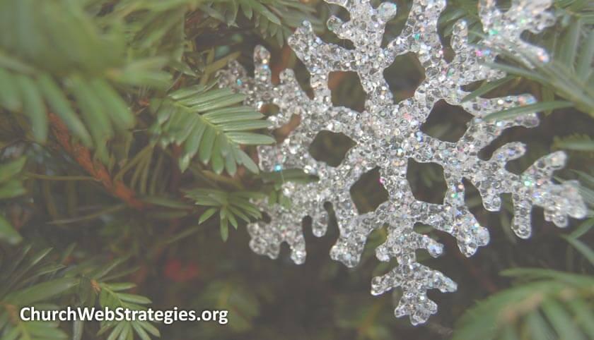 plastic snowflake hanging on pine tree