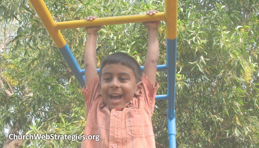 young boy on playground equipment