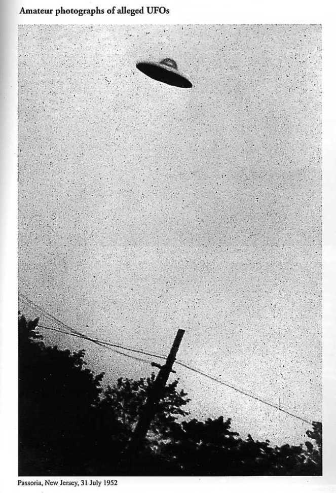 Ein Schwarzweißfoto eines kleinen UFO, das auf der Silhouette von Bäumen und einer Stromleitung fliegt.