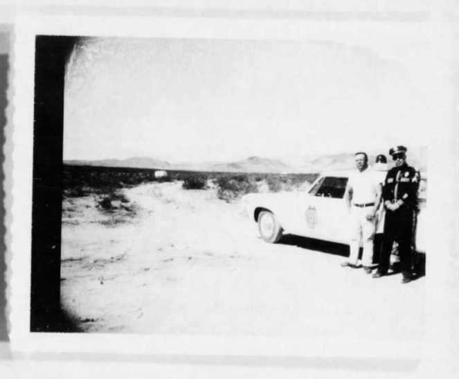 Ein verschwommenes Schwarzweißfoto eines Polizisten und eines Mannes, die vor einem Auto stehen.