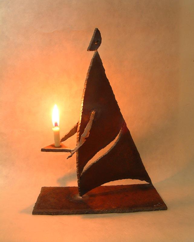 「月のあかり」という鉄の燭台。月の形をした頭部を持つ人のカタチに模したロウソク立てで、灯りを差し出すような佇まいをしています。カタチにより、佑・炬・瑛の3シリーズになっており、祐(ゆう)は、両手を差し伸べて救う、炬(きょ)は、松明のように掲げる火、瑛(えい)は、光り輝く玉という意味があります。暗い中で小さな和蝋燭を灯した状態での写真です。頭部の影が月のカタチに揺れて、個体によってはスリットから漏れる光が日輪となったり、または三日月となったりします。