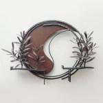 勢いよく伸びるオリーブの枝を鉄で表現した壁面アート作品です。葉は面と線の表現を混在させ、背景に円を切り欠いた面を配置しました。全体写真。