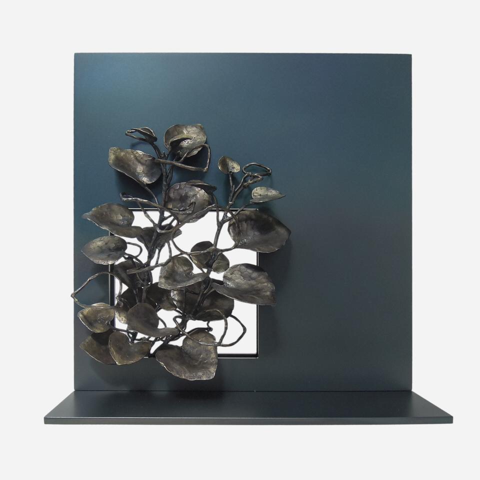 黒焼きした鉄のプレートに開いた窓から、元気の良いポプラの小枝が伸びている様子を、鍛鉄で表現したアート作品です。