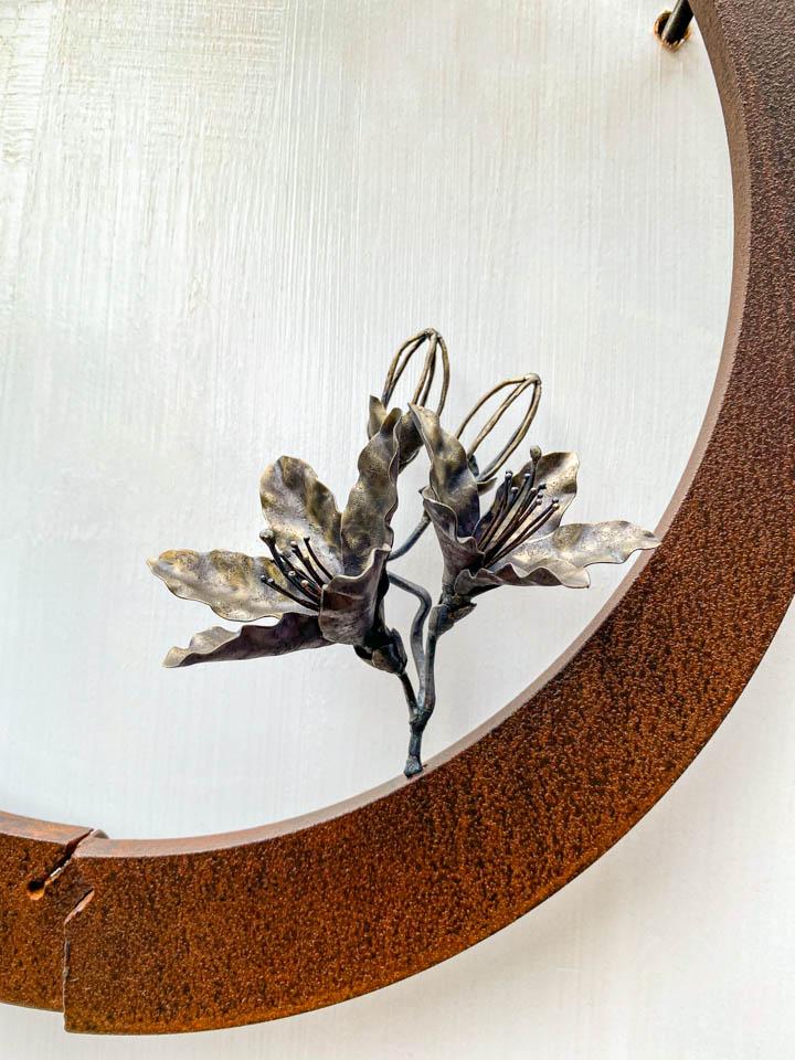 箱根の春を彩るミツバツツジの花を円弧に添えた鉄の彫刻、アート作品です。壁面へ取り付ける仕様になっています。蕾は鍛造した鉄線で表現し軽い印象になっています。円弧は厚みのある鉄を切り出し、下部でズラして表情をつけています。花の様子。