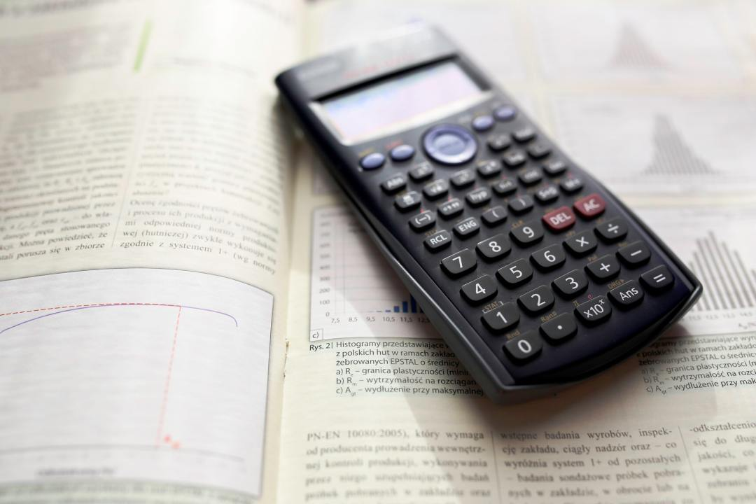 Calculator on Top of an Open Book - k to 12 grading system