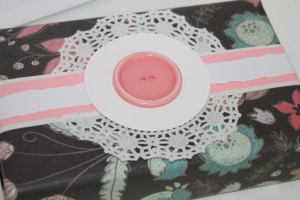 This gift was created using scrapbooking paper. The edges of the paper were folded to create a white board running down the centre of the gift. A pink strip of paper was mounted on top and then a second strip of white paper sits on top of that to create a layered look. I added in a small white doily and big pink button in the center to serve as the focal point in this gift. I love the black-based floral print. The contrast between it and the white and pink creates a beautiful stand-out look.