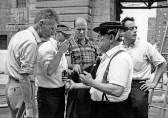 By the Brooklyn Bridge, shooting a scene from FILM BY SAMUEL BECKETT taken in the summer of 1964. Beckett is seen on the far left in his only trip to America, specifically to shoot the film. Director Alan Schneider is wearing the baseball cap and glasses and Buster Keaton is wearing his porkpie hat. NOTFILM, a kino-essay by Ross Lipman tells the story of the making of the film. Produced by Dennis Doros and Amy Heller for Milestone Film & Video.