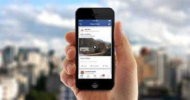 Bir facebook sayfasında görünen video olan telefonu elinde tutan bir el ve arkada bulanık manzara.