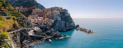 picturesque colorful village on hill on rocky seashore