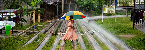 Oil pipelines create a pathway for this young woman through the village of Okrika Town, Nigeria. Photo by Ed Kashi.