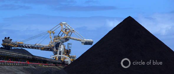 A coal loader eats away at a mountain of black coal at the Port of Newcastle in New South Wales, Australia. In 2011, the mines, trains, and coal loading terminals here shipped about 114 million metric tons of coal on about 1,000 freighters, bringing billions of dollars in export earnings.